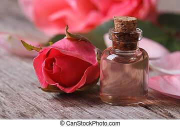 Rose oil in a glass bottle and pink flowers close up...