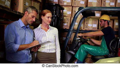 Warehouse management talking with forklift driver behind in...