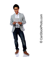 Full length portrait of a happy asian man using tablet...