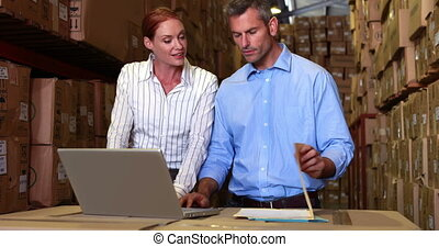 Warehouse management talking and looking at laptop in a...