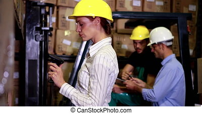 Warehouse manager scanning barcodes on boxes in a large...