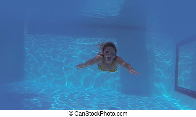 Pretty blonde swimming towards camera and waving filmed with...