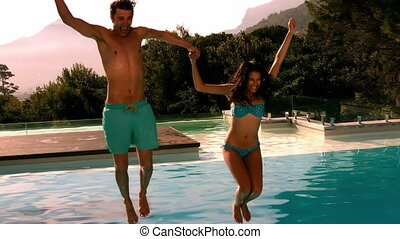Happy couple jumping in swimming pool together in slow...