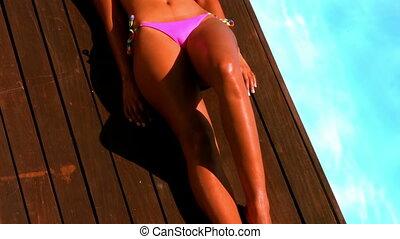 Gorgeous woman in pink bikini lying