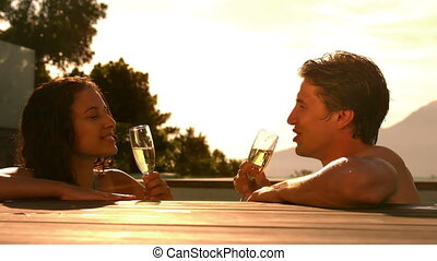 Happy couple drinking champagne together in the swimming...