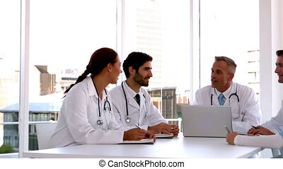 Medical team meeting together with laptop in slow motion