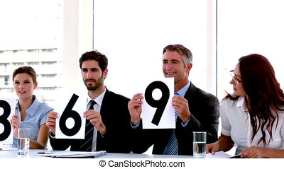 Business people on interview panel showing scores in slow...