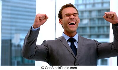 Handsome businessman cheering at camera in slow motion