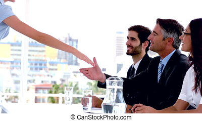 Business people on interview panel shaking hands with...