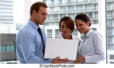 Business team standing and working on laptop together in...