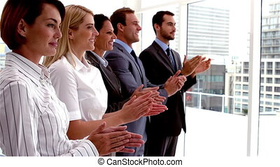 Team of business people clapping in a row in slow motion
