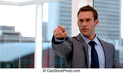Stern handsome businessman pointing ahead in slow motion