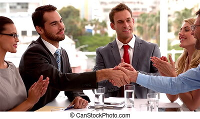 Business team applauding colleagues shaking hands in slow...
