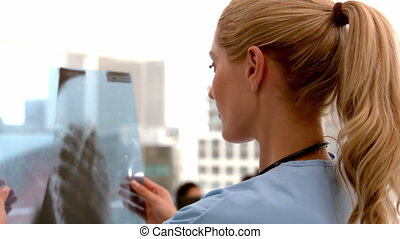 Pretty nurse looking at x-ray in slow motion