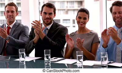 Business team applauding the camera at meeting in slow...