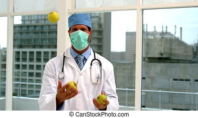 Doctor in mask juggling green apples in slow motion
