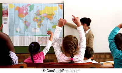 Young pupils raising hands during geography lesson in...