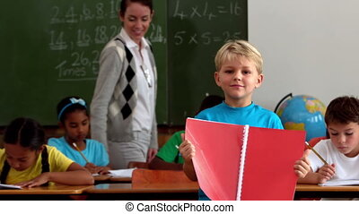 Little boy holding red notepad smiling at camera in...