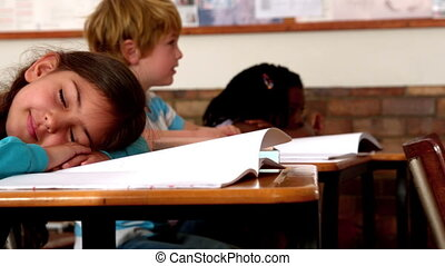 Cute little girl sleeping on desk during class in slow...