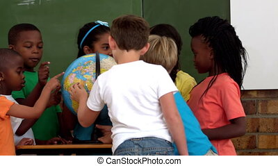 Cute pupils looking at the globe in classroom in slow motion