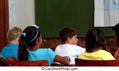 Young pupils raising hands during lesson in classroom in...