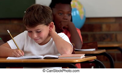 Little boy writing in notepad in classroom and smiling at...