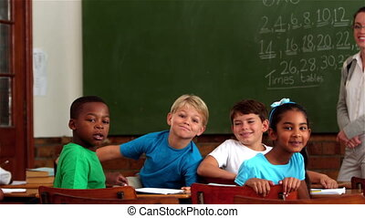 Teacher and pupils smiling at camer - Teacher and young...
