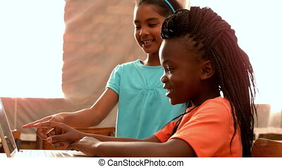 Girls using laptop in classroom - Little girls using laptop...