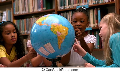 Cute little girls looking at globe in library in slow motion