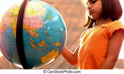 Girl looking at globe in classroom - Little girl looking at...