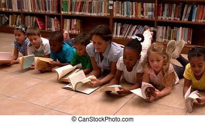 Teacher and pupils reading books on library floor in slow...