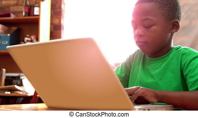 Boy using laptop in classroom - Little boy using laptop in...