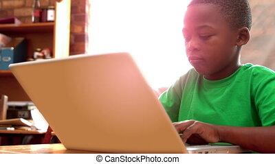 Boy using laptop in classroom - Little boy using laptop in...