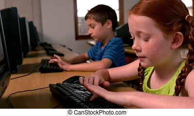 Girl using computer in classroom - Little girl using...