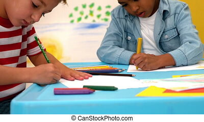 Boys drawing at table in classroom - Cute little boys...
