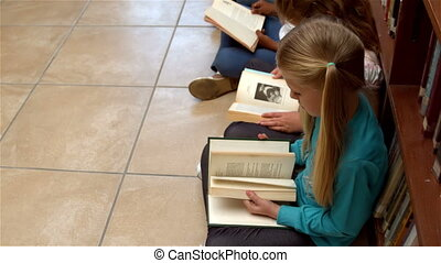 Pupils sitting reading books - Cute pupils sitting on...