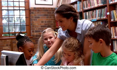 Teacher using computer with pupils - Pretty teacher using...