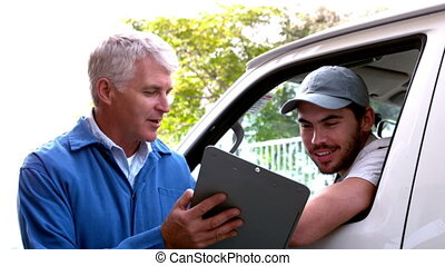 Delivery driver checking his list on clipboard with client...