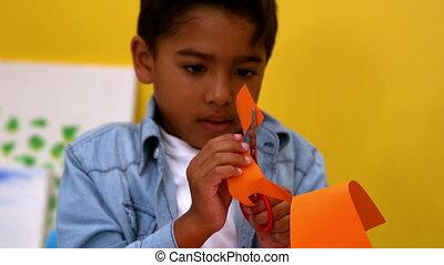 Little boy cutting paper shapes - Cute little boy cutting...