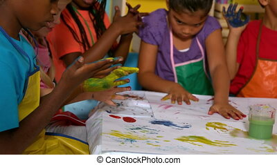 Little pupils painting in classroom