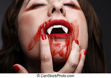 Female vampire licking blood after biting