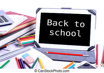 back to school written on a digital tablet with supplies