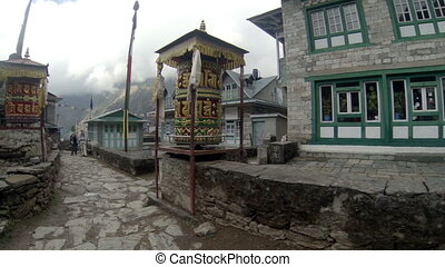 Tourists spins a giant prayer wheel - 27K HIMALAYAS, NEPAL -...