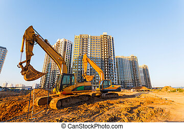 two excavators and a new multistorey building on a...