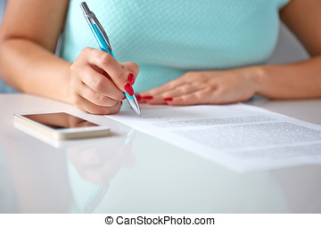 Young woman signs a contract on a white table