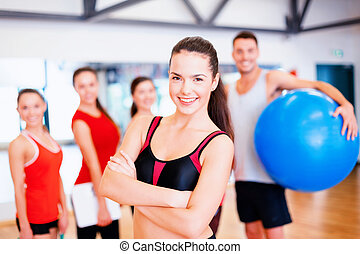 woman standing in front of the group in gym - fitness,...