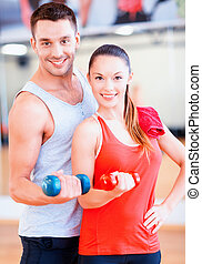 two smiling people working out with dumbbells - fitness,...