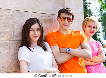 Group of smiling teenagers sitting outdoors