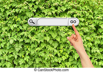 Human hand indicates the search bar in browser Wall of green...