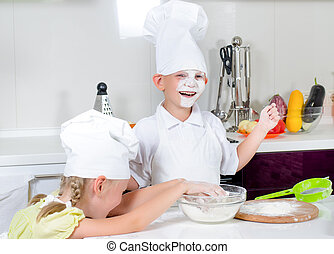Happy little boy and girl baking in the kitchen in their...